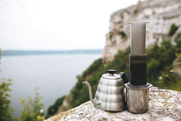 Aeropress next to a metal kettle