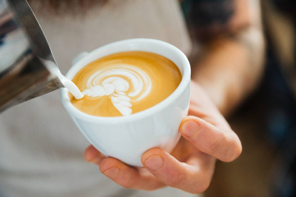 A Barista Pouring Frothed Milk into a Coffee