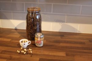 A big jar of coffee beans, peanuts, and peanut butter