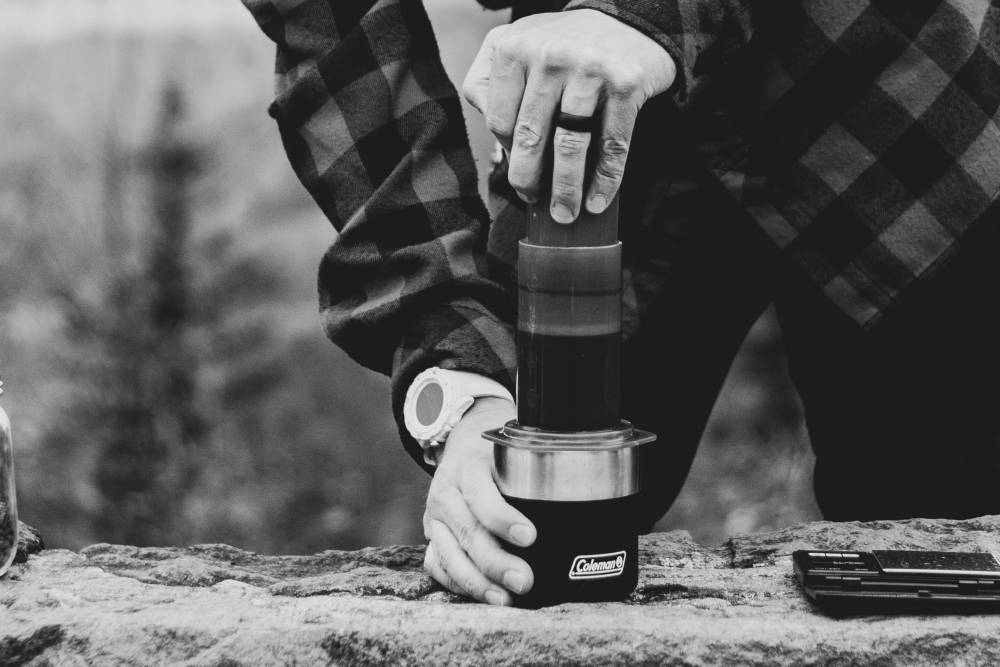 An aeropress being used out in the wilderness