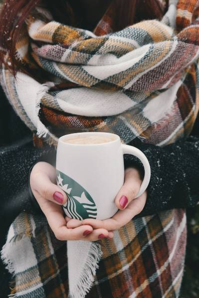 A person holding a big starbucks mug