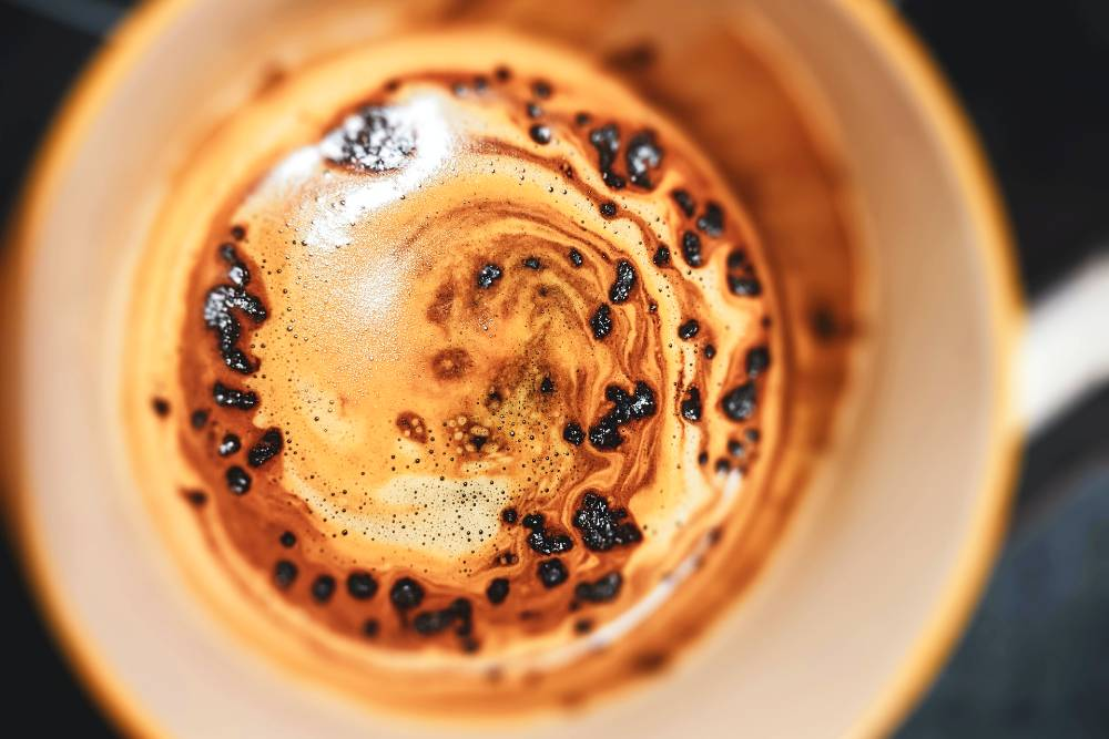 a cup of instant coffee with granules dissolving