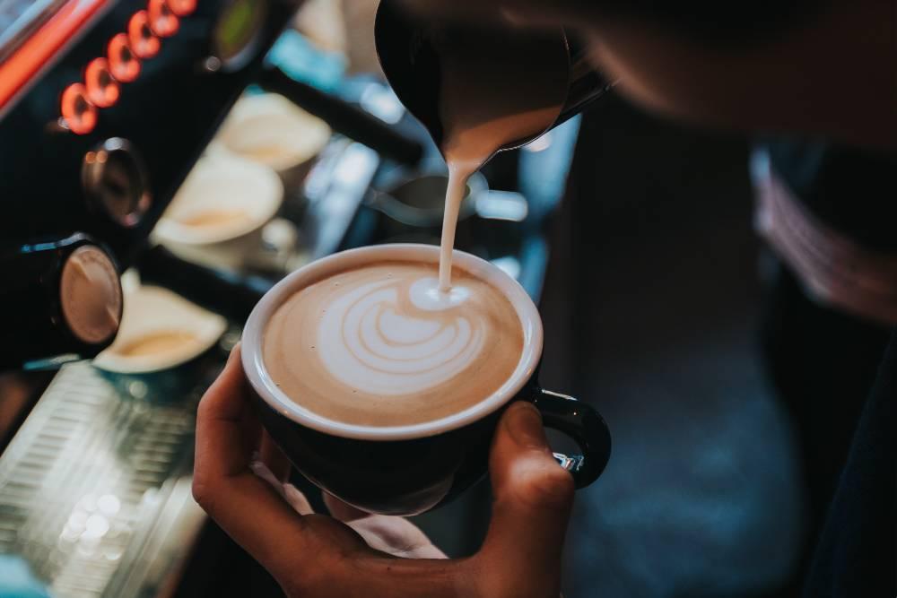 pouring steamed milk into espresso to make a latte