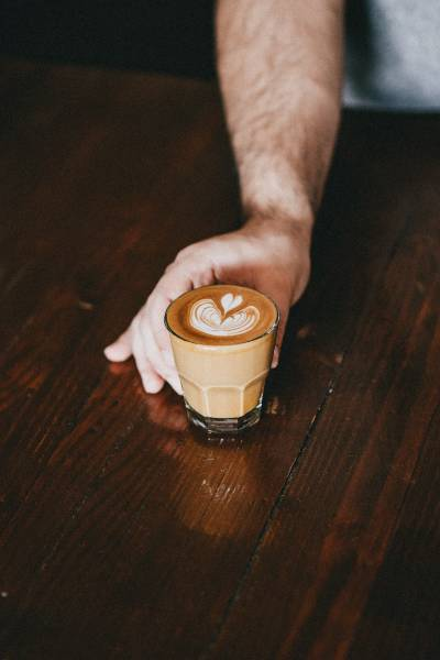 A barista holding a flat white in a glass