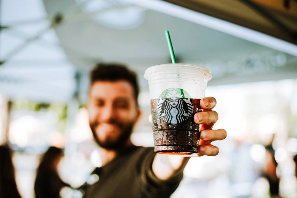 A guy holding a cool iced starbucks coffee
