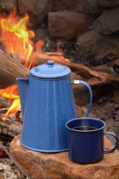 A percolator pot sitting by a fire