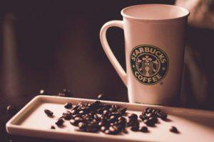 A starbucks mug and some coffee beans
