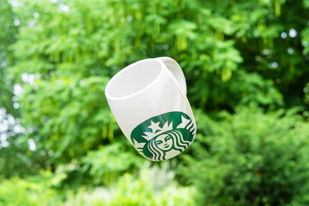 A starbucks mug in mid-air