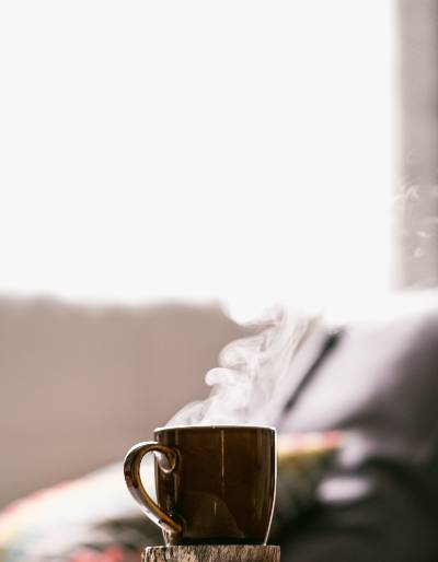 A steaming mug of coffee in front of a couch