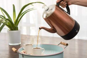 An Electric Percolator Pot Pouring Some Cups of Coffee