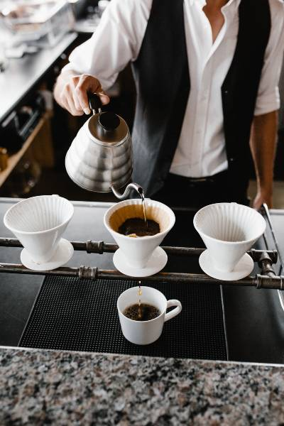 a barista making pour over coffee