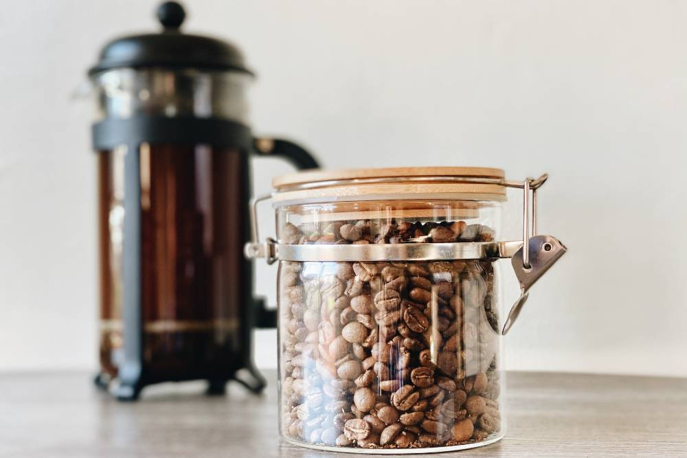 a jar of coffee beans in front of a french press