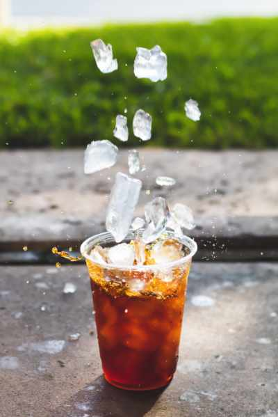 An Iced Coffee with ice cubes falling