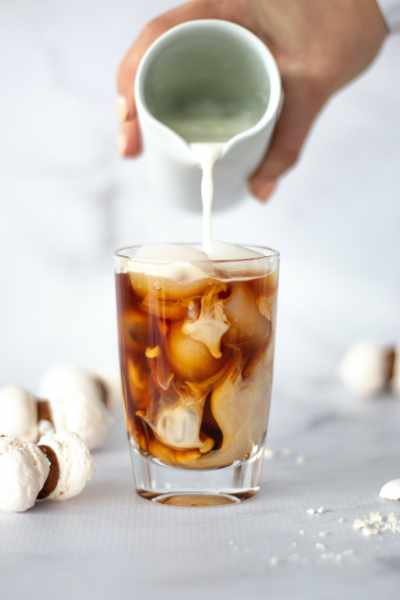Pouring milk into an iced coffee