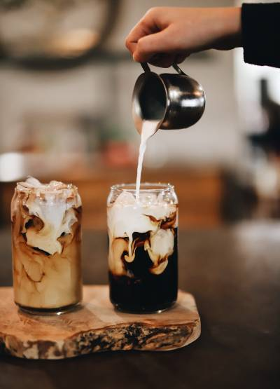 Some milky cold brew coffees being poured
