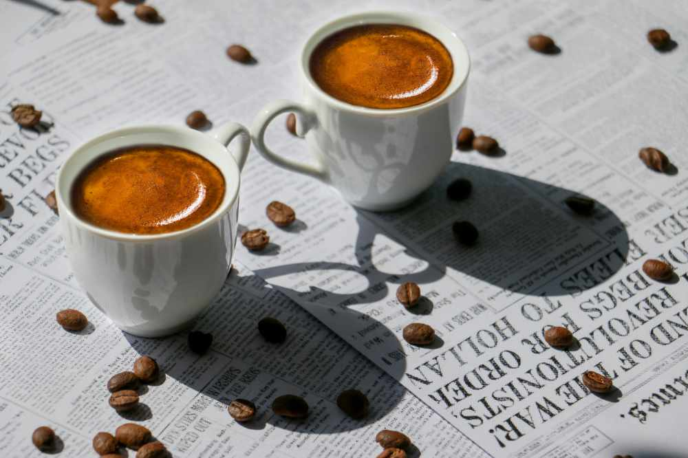 A couple of espresso coffees sitting on a table