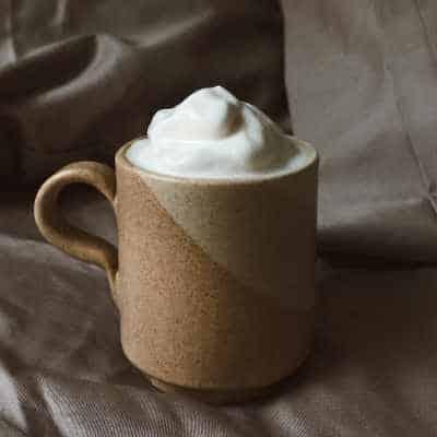 whipped milk in a mug of coffee