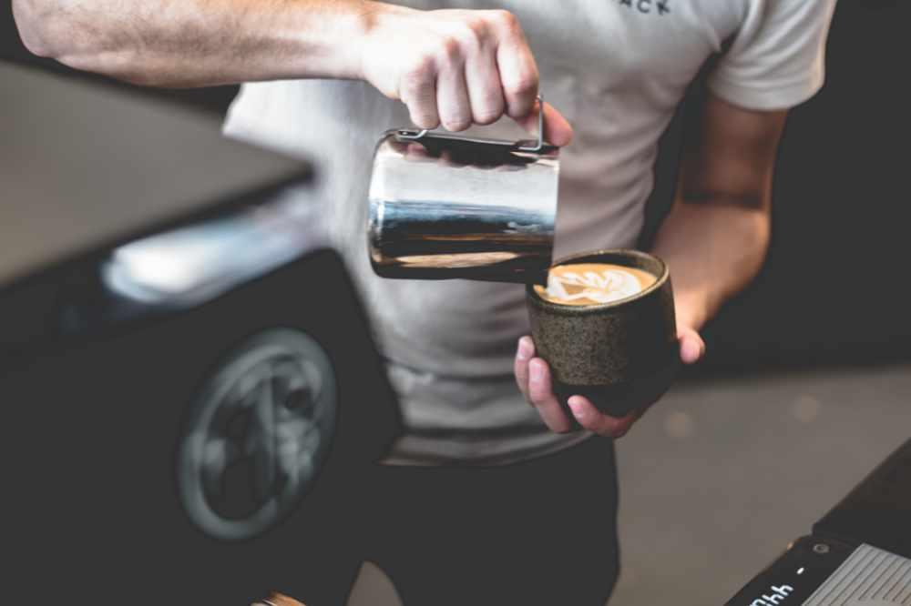 A Barista Pouring Steamed Milk Into Espresso